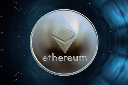 On a blue background in accelerator is gold coin of a virtual digital crypto currency - ethereum for business. Stock Photo