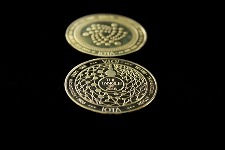 On a black background is isolated the front and back side of gold coin of a digital crypto  currency - iota.
