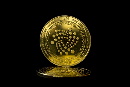 On a black background are coins of a digital crypto  currency iota. In addition to the lying coin, there is standing iota.