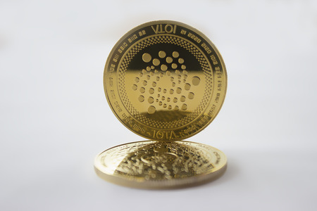 On a white background are coins of a digital crypto  currency iota. In addition to the lying coin, there is standing iota.