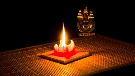 Statue of Tutankhamun lit by a candle on bamboo mat on a black background.