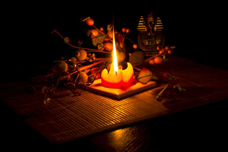 Statue of Tutankhamun and brier lit by a candle on bamboo mat on a black background.