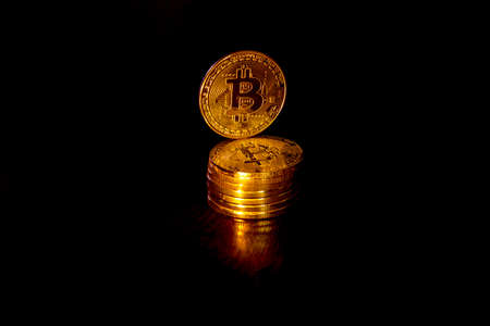 Crypto curency bitcoin gold coins on a black background. In addition to the lying coins, there are standing bitcoin.