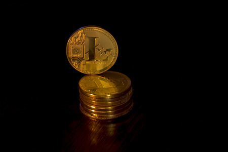 Crypto curency litecoin gold coins on a black background. In addition to the lying coins, there are standing litecoin.