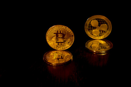 Gold crypto curencies coins bitcoin and ripple on a black background. In addition to the lying coins, there are standing coins.