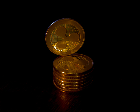 Crypto curency ripple gold coins on a black background. In addition to the lying coins, there are standing ripple.