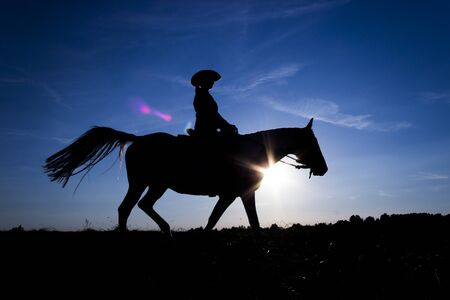 Silhouette cowgirl riding on open plain in western at sunset in blue Stok Fotoğraf