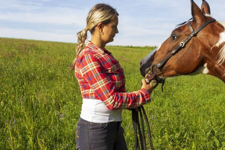 A young girl looks at her horse and the horse looks at his mister