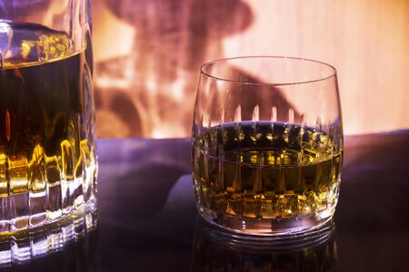 Decanter  and glass with whiskey on a fiery background. Decanter and glass are mirrored on a glass table.