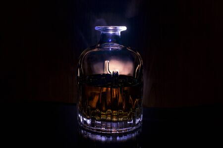 Decanter with whiskey on black background with blue light