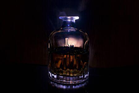 Dekanter mit Whisky auf schwarzem Hintergrund mit blauem Licht