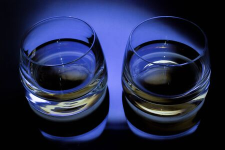 Two glasses with whiskey on black background with blue light