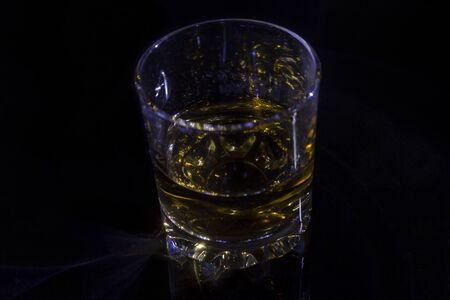 Glass with whiskey on black background in blue light