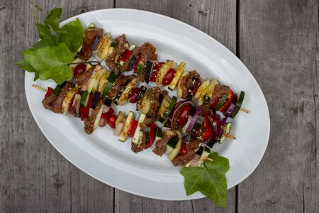 Skewer before grilling composed of bacon onions tomatoes meat pork zucchini peppers on a plate with leaves on a wooden table Фото со стока