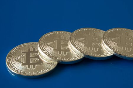 On a blue background with free text space are silver coins of a digital crypto  currencies - bitcoin