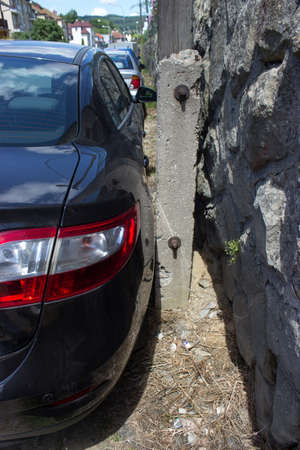 An artistically parked car just a few mm from a concrete pole
