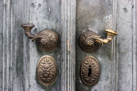 Historic old brass door handle on a wooden door