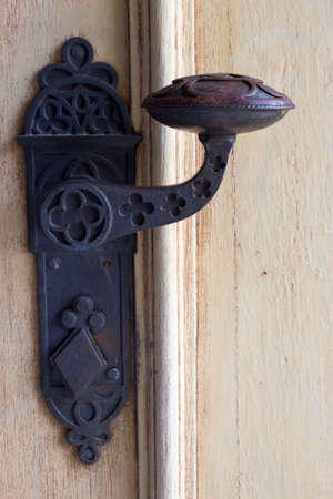 Historic old metal door handle on a wooden door