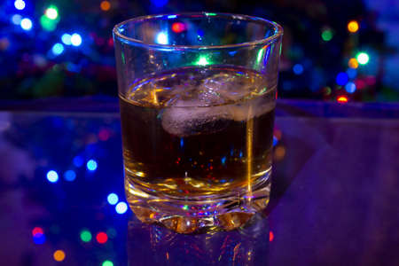 Glass with whiskey and ice cubes on blue background. The Christmas tree is lit in the background. Glass is mirrored on a glass table.