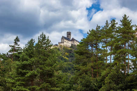 Panoramic view of Bezdez castle in the Czech Republic. In the foreground there are trees, in the background is a hill with castle and there are a white clouds in the blue sky.