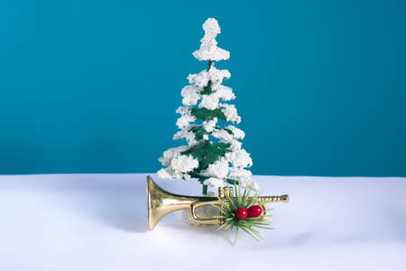 Snowy tree with trumpet festively decorated with a blue background. Christmas still life for musicians. 免版税图像