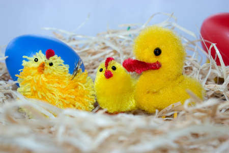 Easter decorations. Chicken, hen and a duck sit on the straw. In the background are colored eggs.