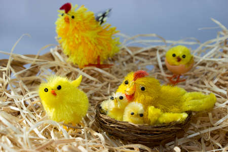 Easter decorations. In the wicker basket are straw chickens. In the brood are too chickens. 免版税图像