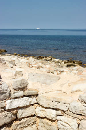 View from the rocky coast with a stone wall to the Adriatic Sea. In the background is a ship. 免版税图像