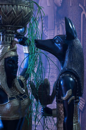 Still life of statues of mythology jackal anubis inpu anup and Cleopatra's Nubian servant with a mask against the virus