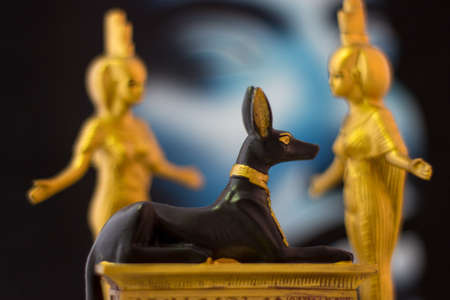 Still life with egyptian figures of anubis and the goddess nebtht and eset in gold.