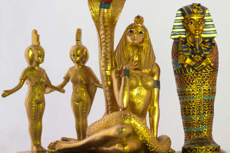 Still life with egyptian figures of the snake, cleopatra, pharaoh and the goddesses nebtht and eset 免版税图像