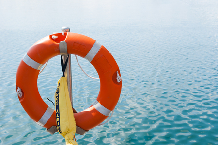 Safety lifebuoy in stand by in front of water