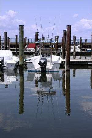 Fishing boat in a marina slip with reflections