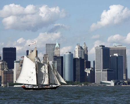 Schooner rigged sailboat in New York Harbor with Lower Manhattan in the background.