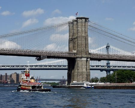 Tugboat going up the East River past Brooklyn and Manhattan bridges in New York City. Stock Photo