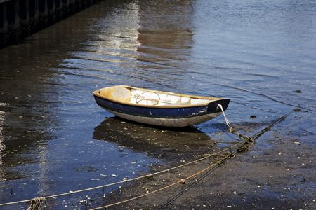 Old rowboat moored in a harbor at low tide photo