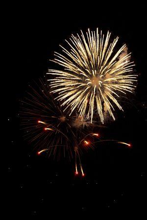 Three bursting fireworks shells on a dark night