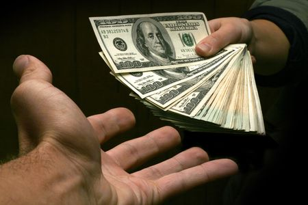 handing over: A stack of cash being handed over from one hand to another.