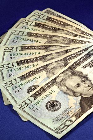 fan shaped: A closeup of twenty dollar bills shaped like a fan on a blue background