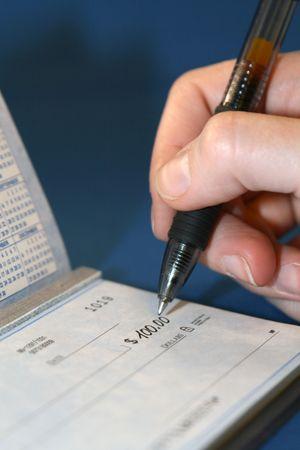 A closeup of a person writing a personal Check