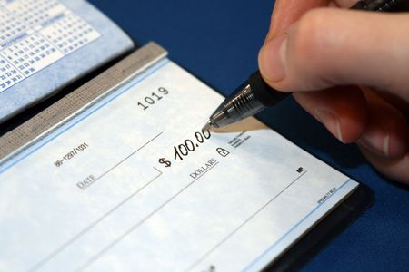 payable: Writing a check in order to pay bills Stock Photo