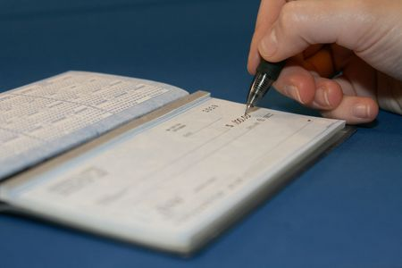 payable: Writing a check in order to pay bills on blue background Stock Photo