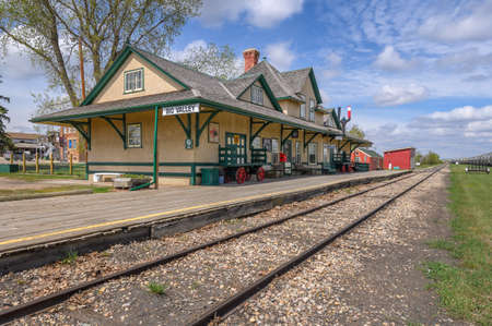 Big Valley, Alberta, Canada, May 19, 2020 - Exterior view of the railway station with platform and train tracks
