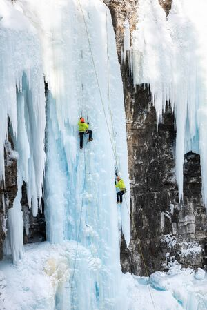 Ice climbers on frozen Upper Falls in Johnston Canyon in Banff National Park