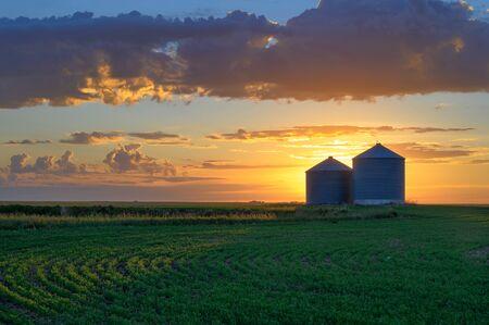 Prairie sunrise on metal grain bins near the city of Moose Jaw, Saskatchewan, Canada
