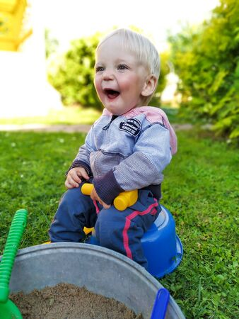 happy little boy with a little yellow plastic hammer sitting near the sandbox in the green backyard on a sunny summer day