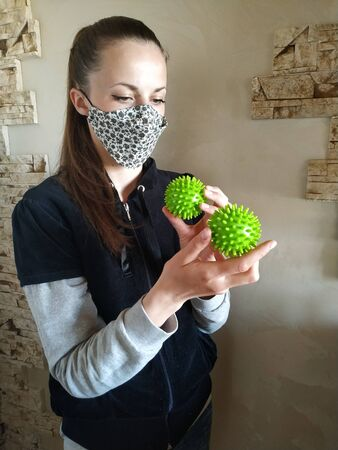 A beautiful girl in medical mask looks holding green massage balls in her hands similar to coronovirus molecules