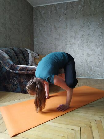 girl practices yoga at home. handstand in Bakasana. Crane Pose. Crow Pose