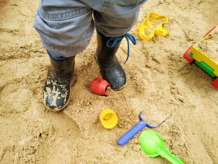 child feet in small rubber boots stained in sand in a sandbox among toys. close up Stock fotó