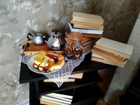 fresh hot cheese cake, sugar bowl and teapot with tea on the table with books.